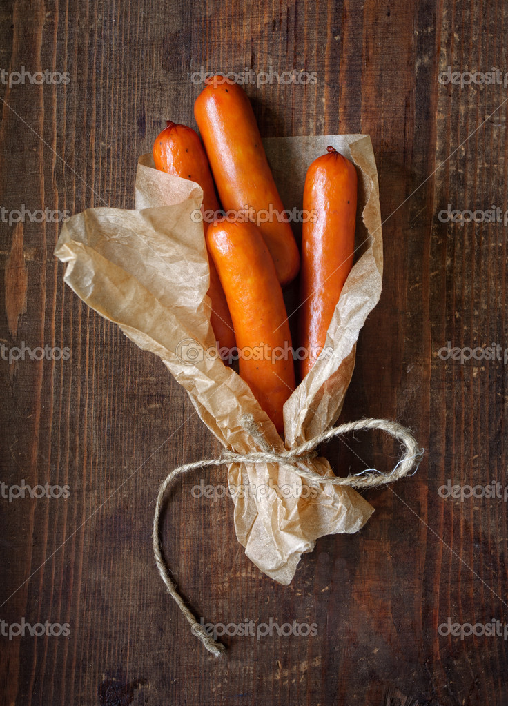 Sausages wrapped in paper on the wooden surface — Stock Photo #11153105