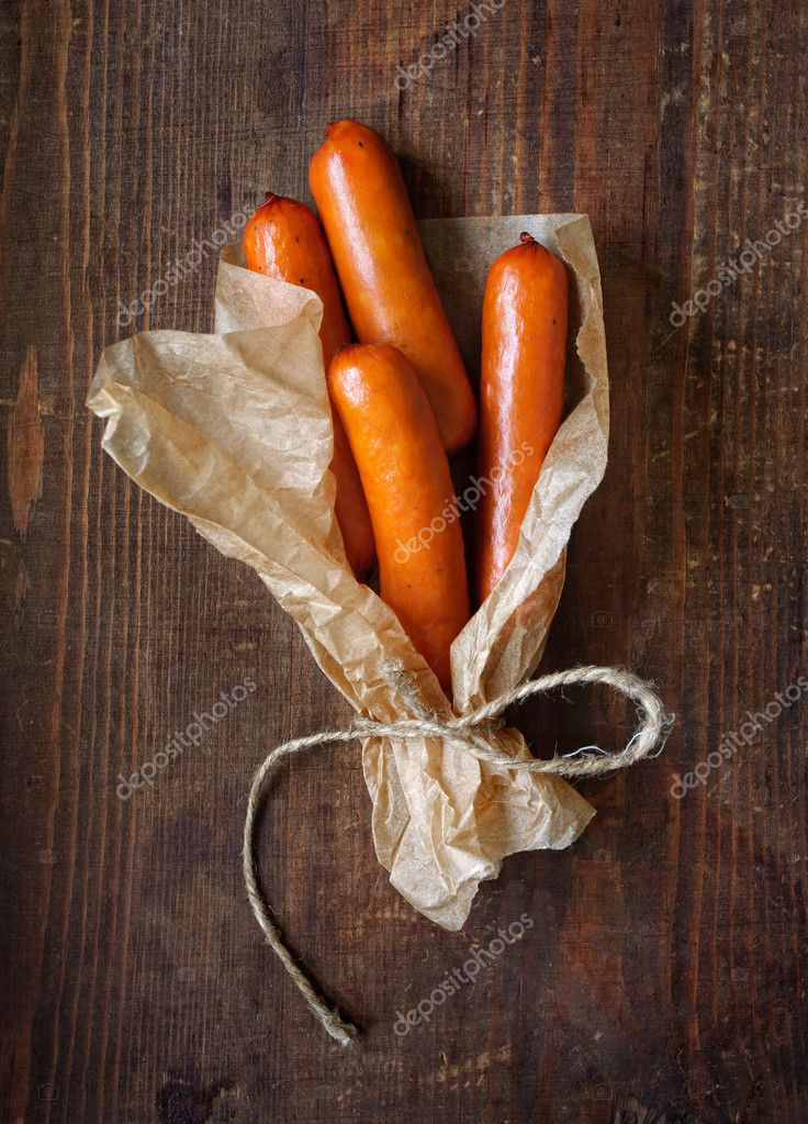 Sausages wrapped in paper on the wooden surface — Stok fotoğraf #11153105