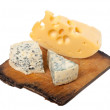 Various types of cheese on old wooden kitchen board — Stock Photo #12184525