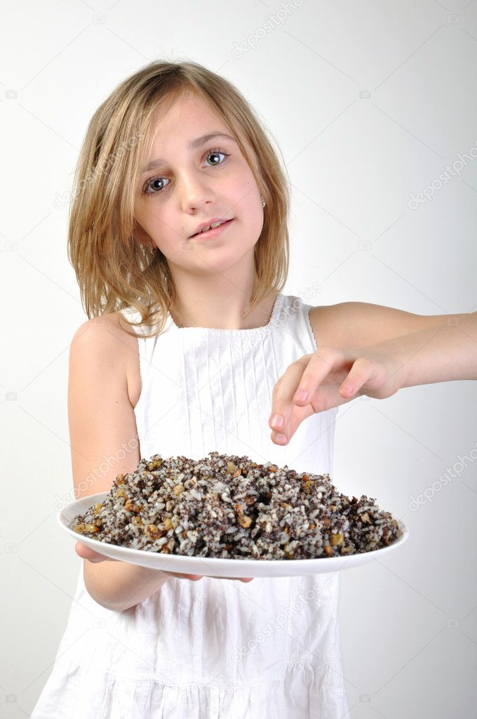 Child with traditional European Christmas food kutia made of wheat or rice, poppyseeds, nuts, raisins and honey — Stock Photo #11064053