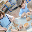 Group of children shaping clay in pottery studio — Stock Photo #11809790