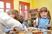 Groep kinderen versieren hun aardewerk klei — Stockfoto