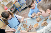 Group of children shaping clay in pottery studio — Stock Photo
