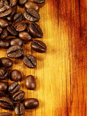 Coffee beans on the wooden desk as food background — Stock Photo