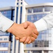 Handshake with modern skyscrapers as background — Stock Photo