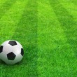 Green striped football field with soccer ball — Stock Photo