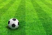 Groene gestreepte voetbalveld met voetbal — Stockfoto