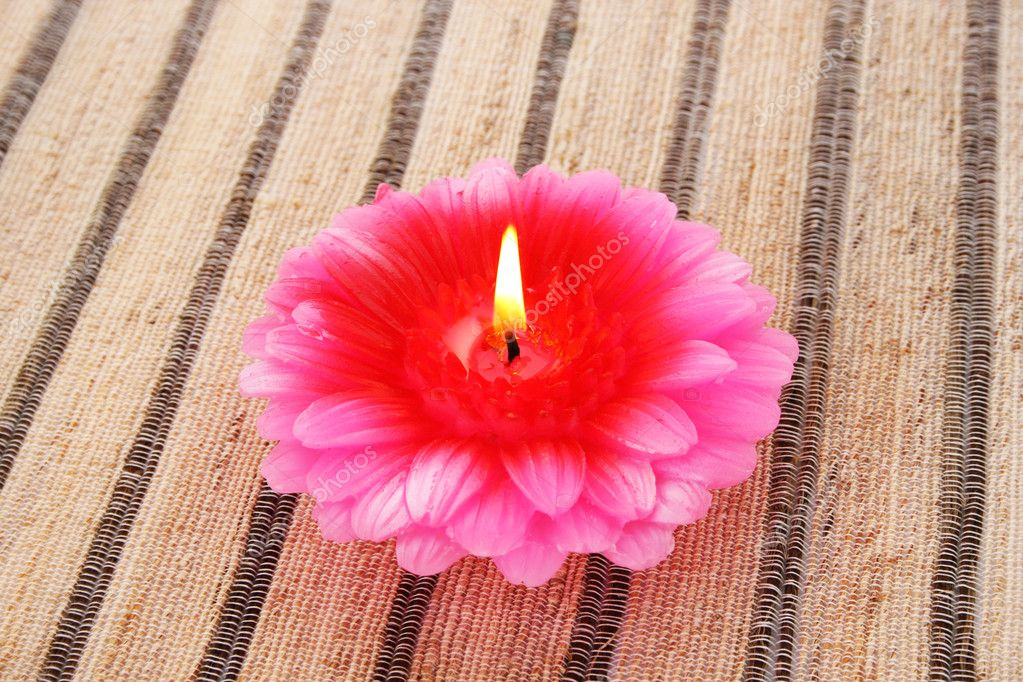 Pink flower candle on striped mat. — Lizenzfreies Foto #10740762