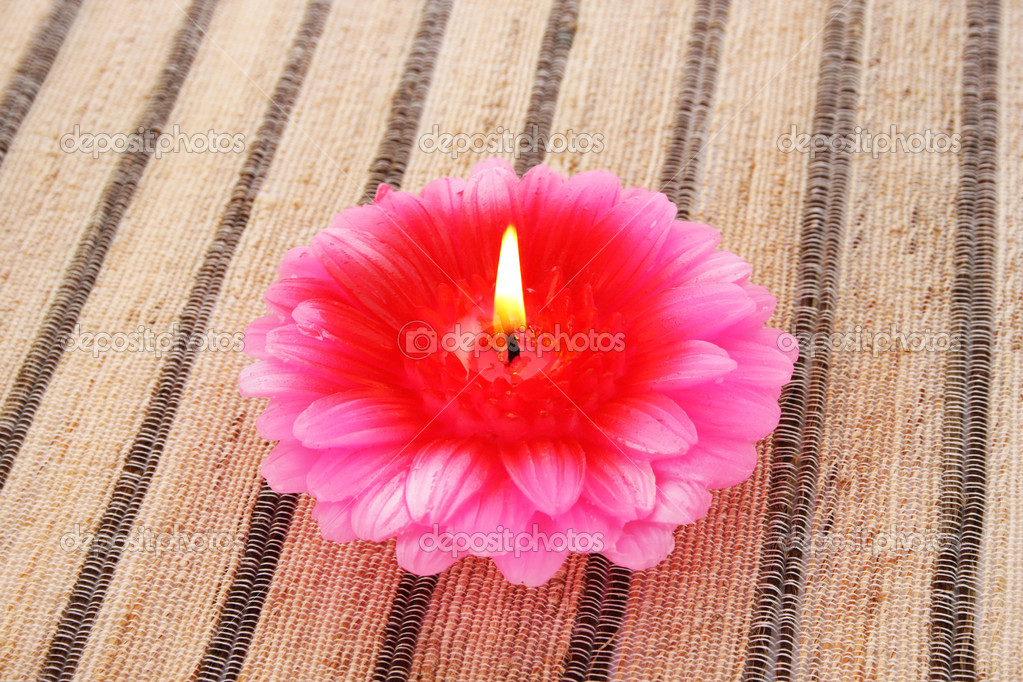 Pink flower candle on striped mat.  Photo #10740762