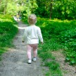 Little girl walking in forest — Stock Photo