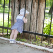 Little girl near fence — Stock Photo