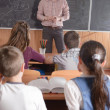 Young teacher in front of class — Stock Photo