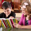 Smiling boy and girl reading book at school — Stock Photo