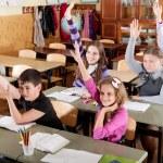 Schoolchildren raising hands — Stock Photo