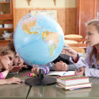 Schoolchildren exploring globe in classroom — Stock Photo