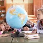Schoolchildren exploring globe in classroom — Stock Photo