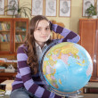 Pretty girl with globe in classroom — Stock Photo
