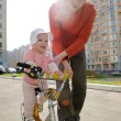 Father helping his daughter riding bicycle — Stock Photo #11692426