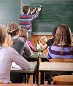 Jeune enseignant de sexe masculin expliquant les maths au tableau noir — Photo
