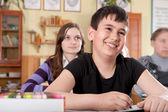 Niño sonriente durante la lección en la escuela — Foto de Stock
