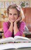 Cute girl reading book in classroom at school — Stock Photo