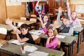 Schoolchildren raising hands — Stock Photo