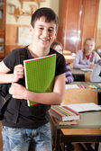 Smiling boy in front of class — Stock Photo