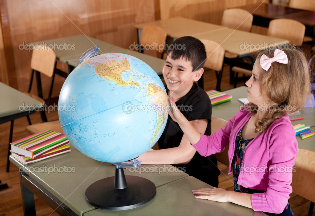 Schoolchildren are exploring globe in classroom during lesson  Stock Photo #11692423