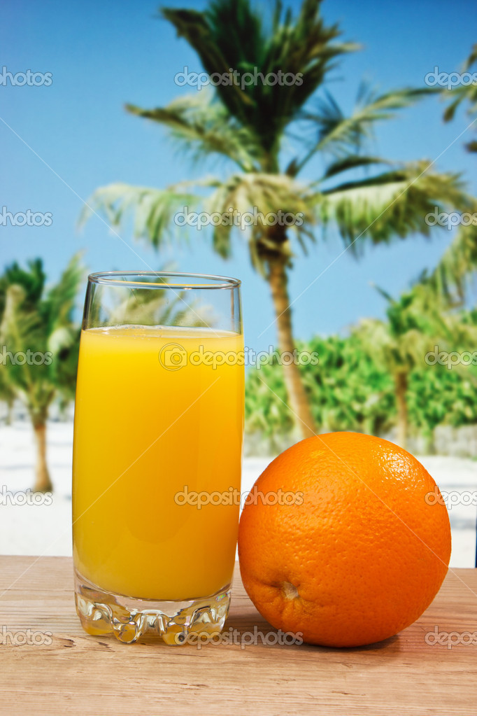 Glass of orange juice on a beach table  Stock Photo #12045020