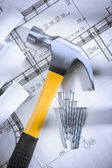 Claw hammer and nails with blueprints — Stock Photo