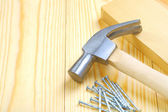 Hammer with nails and plank — Stock Photo