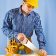 Stock Photo: Carpenter works with handsaw