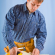 Stock Photo: Carpenter does measurement