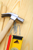 Claw hammer with nails and pencil on level — Stock Photo