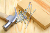 Claw hammer with nails and timber on table — Stock Photo