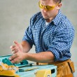 Foto Stock: Men works on woodworking mashine