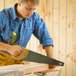 Stock Photo: Worker works with handsaw