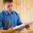 Carpenter looks on the blueprint — Stock Photo