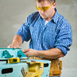 Young men adjusts woodworking mashine - Stock Photo