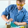 Worker adjusts the woodworking mashine - Stock Photo