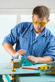 Worker adjusts the woodworking mashine — Stock Photo