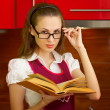 Young girl with a book on kitchen — Stock Photo