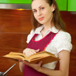 Woman reading a cookbook on kitchen — Stock Photo