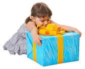 Happy child embraces large birthday gift — Stock Photo