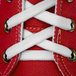 Royalty-Free Stock Photo: White lace on red sneakers