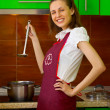 Cheerful young woman preparing food on kitchen — Stock Photo