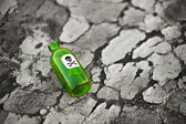 Bottle on poisoned ground — Stock Photo
