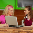Young women in the kitchen with a laptop — Stock Photo