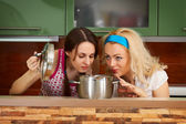 Two young women with a pot of soup — Stock Photo