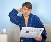 Person reads a newspaper with pensiveness — Stock Photo